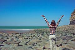 Kvinna som lyfter hennes armar på stranden Arkivfoto