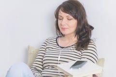Kvinna som lyssnar en audiobook royaltyfri foto