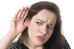 Kvinna som lyssnar med hennes hand på ett öra Arkivbild