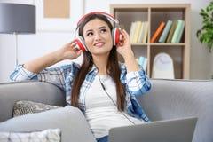 Kvinna som lyssnar till audiobook till och med hörlurar Royaltyfri Bild