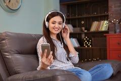 Kvinna som lyssnar till audiobook till och med hörlurar Arkivfoton