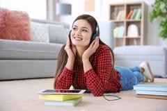 Kvinna som lyssnar till audiobook till och med hörlurar Arkivbild