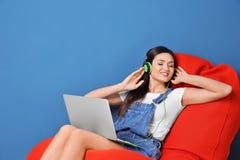Kvinna som lyssnar till audiobook till och med hörlurar Royaltyfria Foton
