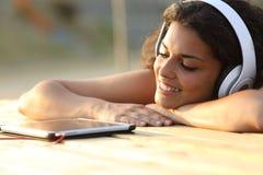 Kvinna som lyssnar till musik från en minnestavla Arkivbild