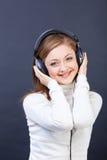 Kvinna som lyssnar till musik i hörlurar Arkivbilder