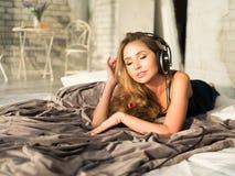 Kvinna som lyssnar till musik med hörlurar som läggas på hennes säng Fotografering för Bildbyråer
