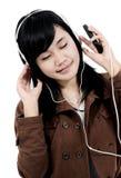 Kvinna som lyssnar till musik med telefonen Royaltyfria Foton