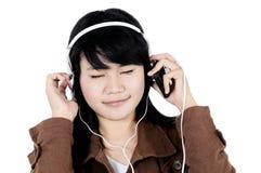 Kvinna som lyssnar till musik med telefonen och har gyckel Royaltyfria Foton