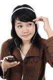 Kvinna som lyssnar till musik med telefonen och har gyckel Arkivbild