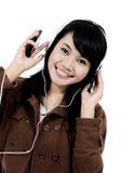 Kvinna som lyssnar till musik med telefonen och har gyckel Arkivfoton