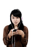 Kvinna som lyssnar till musik med telefonen och har gyckel Royaltyfria Bilder
