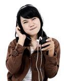Kvinna som lyssnar till musik med telefonen och har gyckel Arkivbilder