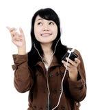 Kvinna som lyssnar till musik med telefonen och har gyckel Royaltyfri Foto