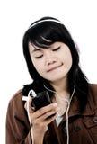 Kvinna som lyssnar till musik med telefonen och har gyckel Arkivfoto