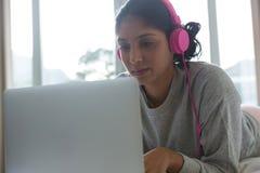 Kvinna som lyssnar till musik, medan genom att använda bärbara datorn på säng arkivfoto