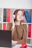 Kvinna som lyssnar till musik på kontoret Ögon som stängs av nöje royaltyfri fotografi