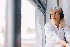 Kvinna som lyssnar till musik som ut stirrar fönstret arkivbild
