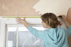 Kvinna som mäter fönsterramen med bandet royaltyfri foto