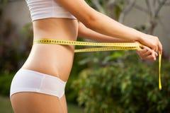 Kvinna som mäter henne waistline. Göra perfekt slankt förkroppsligar arkivfoto