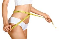 Kvinna som mäter henne waistline. Perfect den slanka huvuddelen Arkivbild