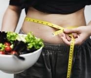 Kvinna som mäter hennes mage och vikt arkivfoton