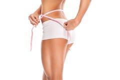 Kvinna som mäter hennes slanka kropp som isoleras på vit bakgrund Royaltyfri Bild