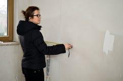 Kvinna som mäter i nytt badrum Arkivfoton