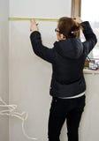 Kvinna som mäter i nytt badrum royaltyfri bild