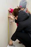 Kvinna som mäter i nytt badrum Arkivbilder