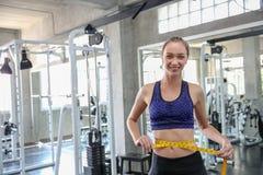 Kvinna som mäter midjan i idrottshall Slank kvinna som mäter hennes tunna wais royaltyfri bild