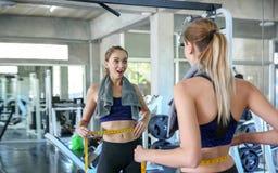 Kvinna som mäter midjan i idrottshall Slank kvinna som mäter hennes tunna wais arkivfoton