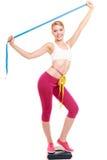 Kvinna som mäter på vägningsskala med lyftta armar Fotografering för Bildbyråer