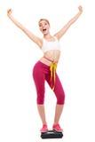 Kvinna som mäter på vägningsskala med lyftta armar Royaltyfri Bild