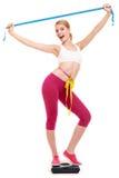 Kvinna som mäter på vägningsskala med lyftta armar Royaltyfri Foto