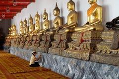 Kvinna som målar buddha statyer i Wat Pho Temple bangkok thailand fotografering för bildbyråer