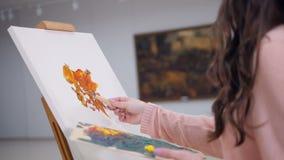 Kvinna som målar en bild som applicerar målarfärg på kanfas stock video