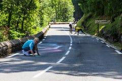 Kvinna som målar vägen till Cold'Aubisque Royaltyfri Bild