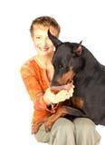 Kvinna som matar den hungriga älsklings- hunden vid den röda kaviaren Arkivbild