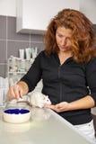 Kvinna som matar en tjalla på veterinären Arkivfoto
