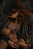 Kvinna som matar hennes lilla son Arkivfoto