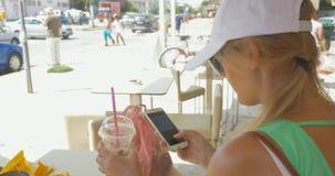Kvinna som meddelar i mobil budbärare arkivfilmer