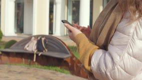 Kvinna som meddelar på smartphonen lager videofilmer