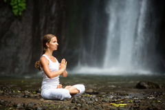 Kvinna som mediterar göra yoga mellan vattenfall Arkivbild