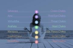 Kvinna som mediterar i den utomhus- lotusblommapositionen Chakra ljus över henne kropp arkivfoto