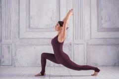 Kvinna som mediterar i en idrottshall Stå i krigare en posera, Virabhadrasana Sportig ung kvinna som gör yogaövning på ljus arkivbilder