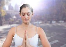 Kvinna som mediterar mot den oskarpa gatan med signalljuset Arkivfoto