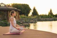 Kvinna som mediterar nära sjön Royaltyfri Fotografi