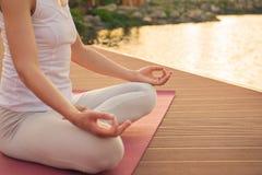 Kvinna som mediterar nära sjön Arkivfoto