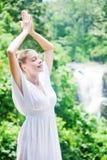 Kvinna som mediterar nära vattenfallet Fotografering för Bildbyråer