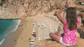 Kvinna som mediterar på den ovannämnda sandstranden för klippa arkivfilmer